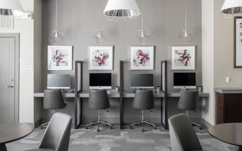 large windows and stylized lighting fixtures brighten business center with desktop stations