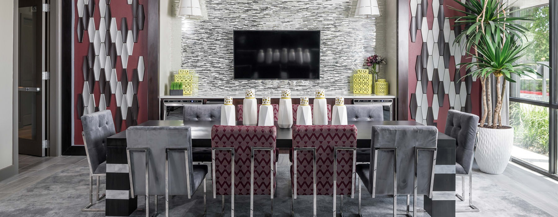 clubhouse kitchen area with long table surrounded by chairs and pendant lighting
