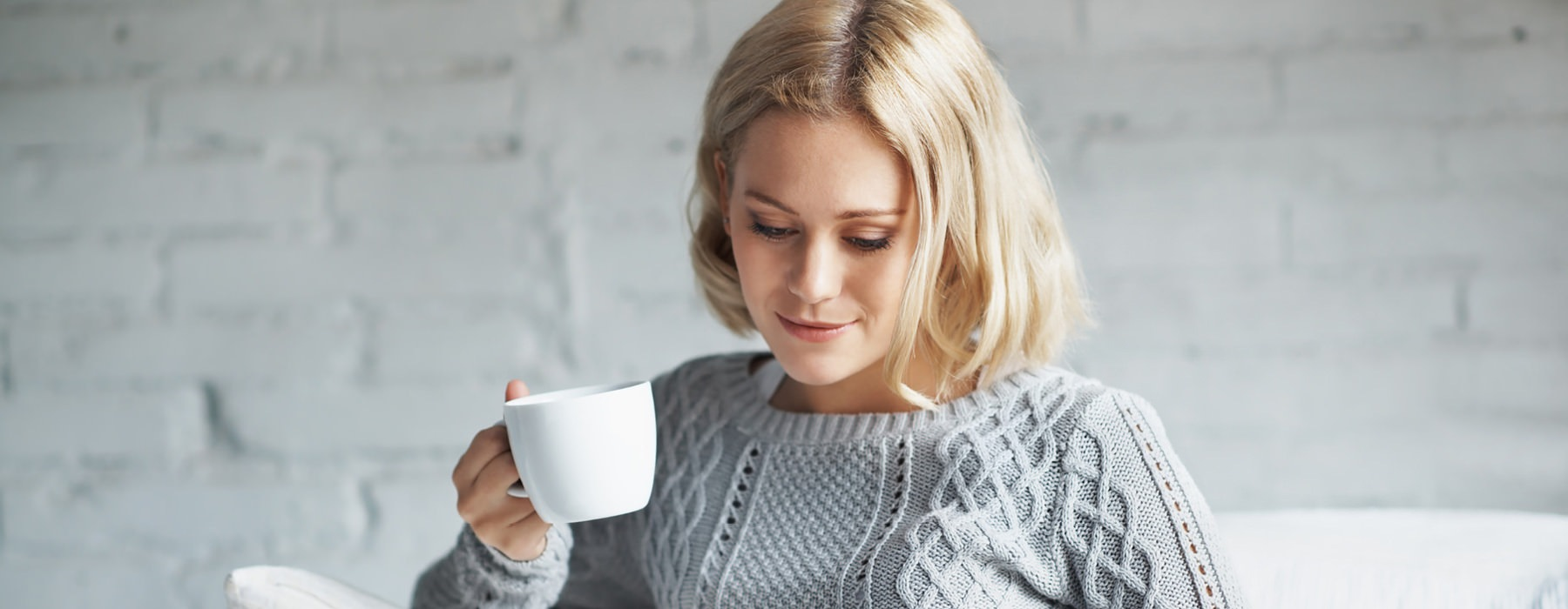 woman smiling on couch holding a cup of coffee